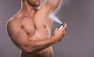 デオドラント剤を脇に使用する男性